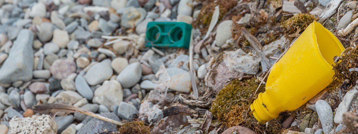 Closeup of bits of plastic trash laying on a rocky beach in Svalbard.